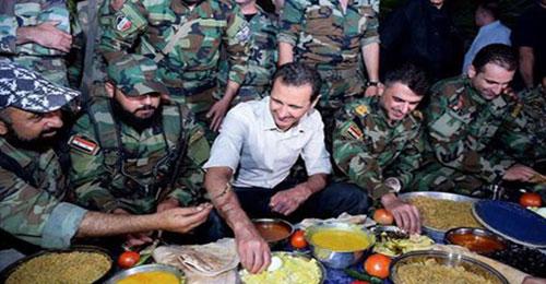 """بالصور: الاسد يتناول """"أطيب لقمة في حياته""""…  وشعبه يموت جوعاً"""