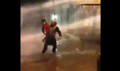 بالفيديو: متظاهر يحمل ابنه متحدياً خراطيم المياه