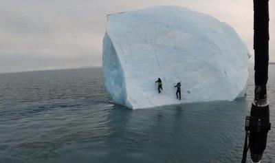 بالفيديو: جبل جليدي ينقلب عليهما